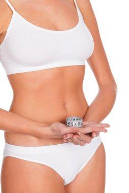 Slim woman in white underwear with tape measure, copyspace