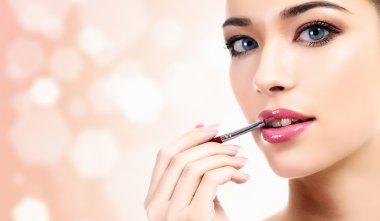 Woman applying lips makeup