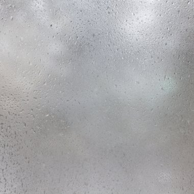 Frozen drops on frosted glass. Winter textured background.