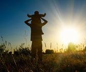 Silueta otec a syn při západu slunce