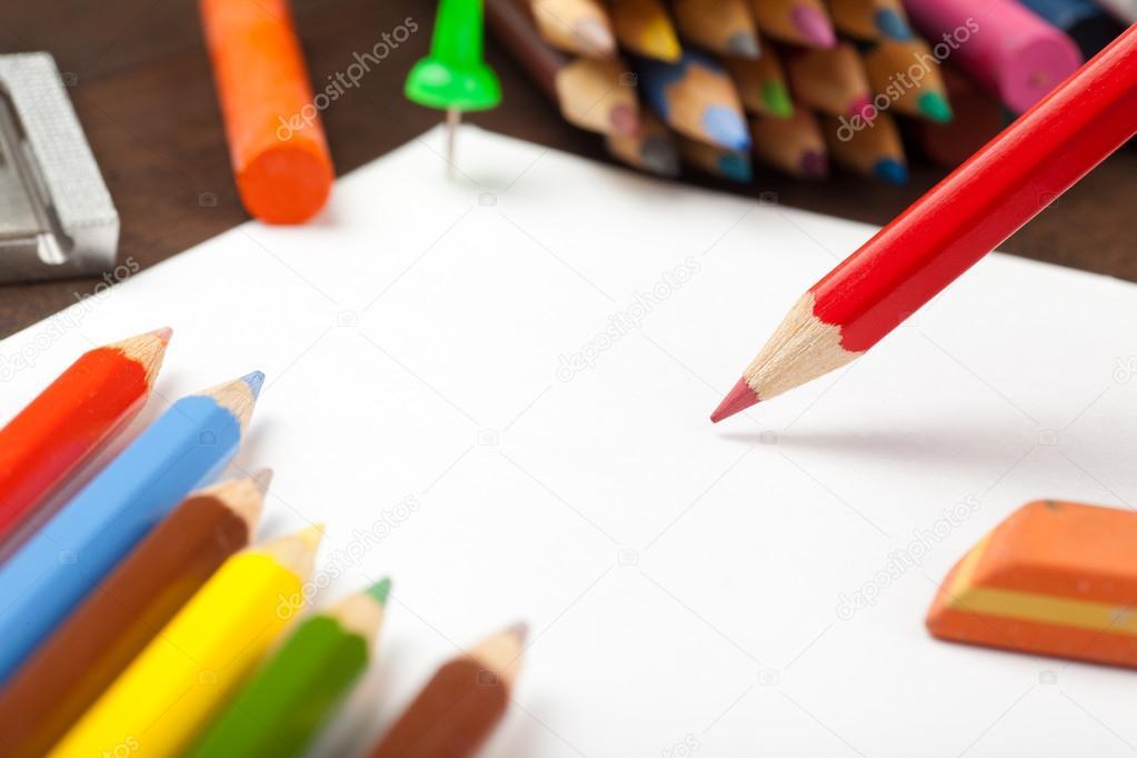 lápiz rojo se basa en la hoja de papel blanco. lápices de colores ...