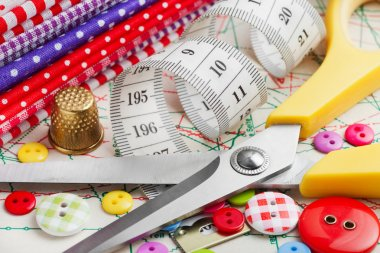 Sewing items: buttons, colorful fabrics, scissors, measuring tap