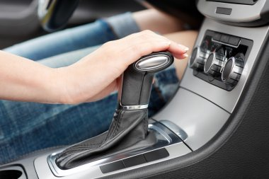 Hand on automatic gear shift, woman in luxury car