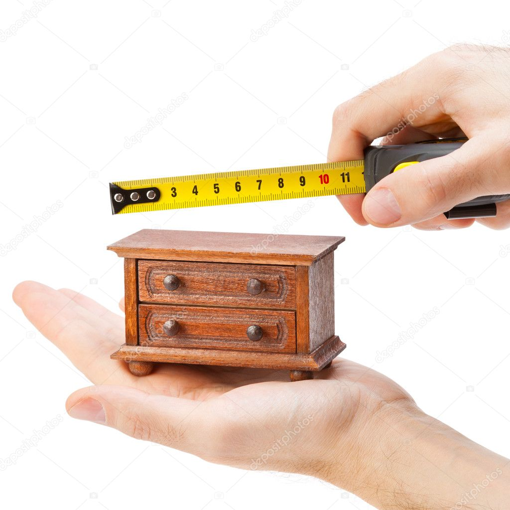 Woodworker measuring chest of drawers with a tape measure, carpe