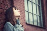 Fotografia pensosa bella ragazza in piedi vicino a un muro di mattoni