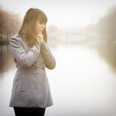 pretty sad girl in cold weather near river in a fog