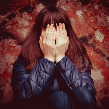 Girl with hands over eyes near wall outdoors