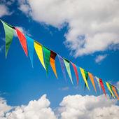 více barevné trojúhelníkové vlajky na pozadí modré oblohy