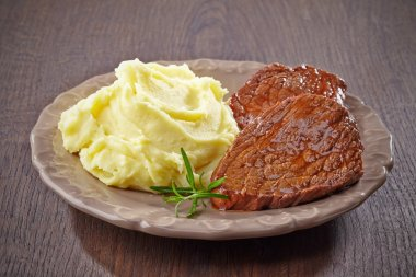 mashed potatoes and beef steak on plate