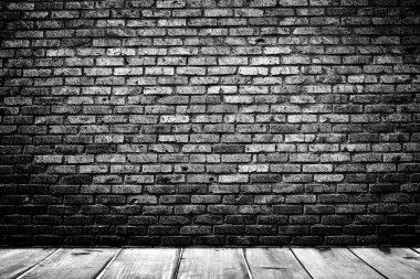 Dark room with wooden floor and brick wall background