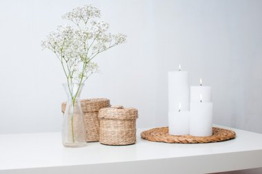 flowers, white candles and two closed baskets