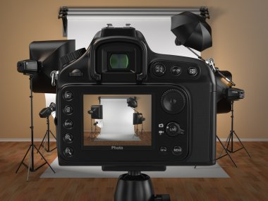 Digital photo camera in studio with softbox and flashes