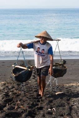 Traditional sea salt production on the volcanic black sand, Bali