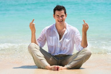 Middle finger gesture by man on a beach