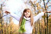 holčička s rukama nahoře v podzimním lese