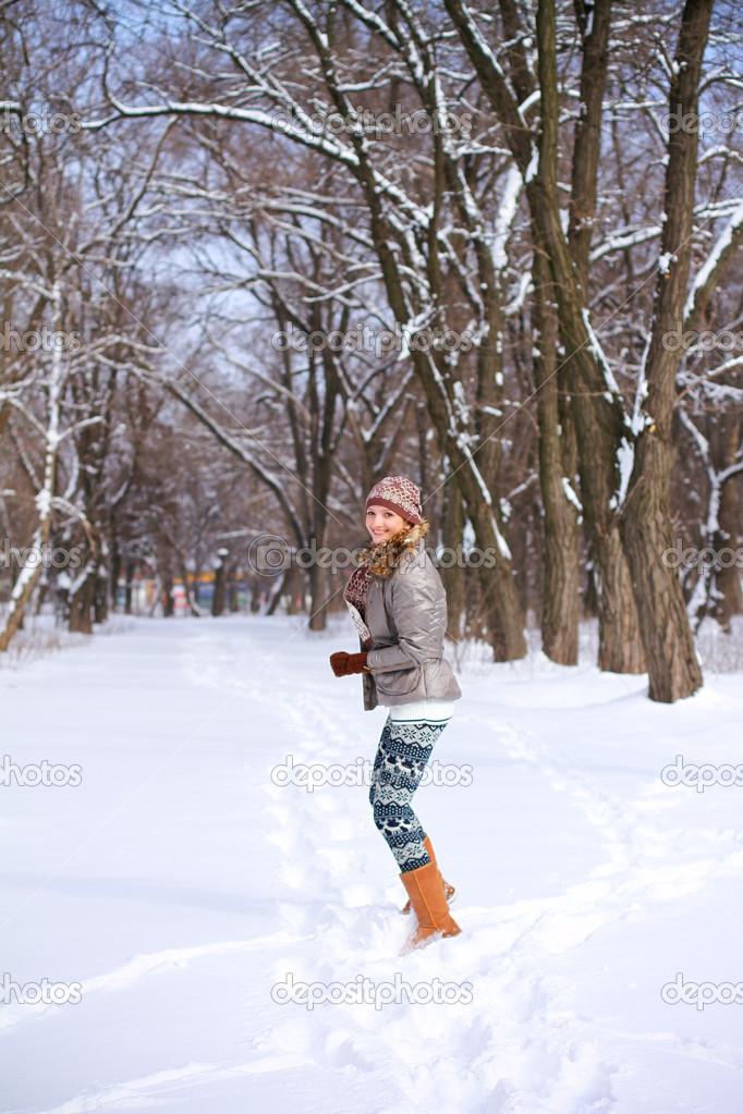 chica rubia sonriente jugando y corriendo por la nieve en un parque de invierno u foto de majesticca