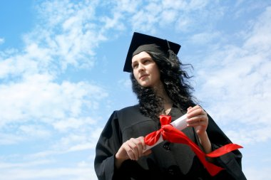 Happy graduate student in cloak with diploma