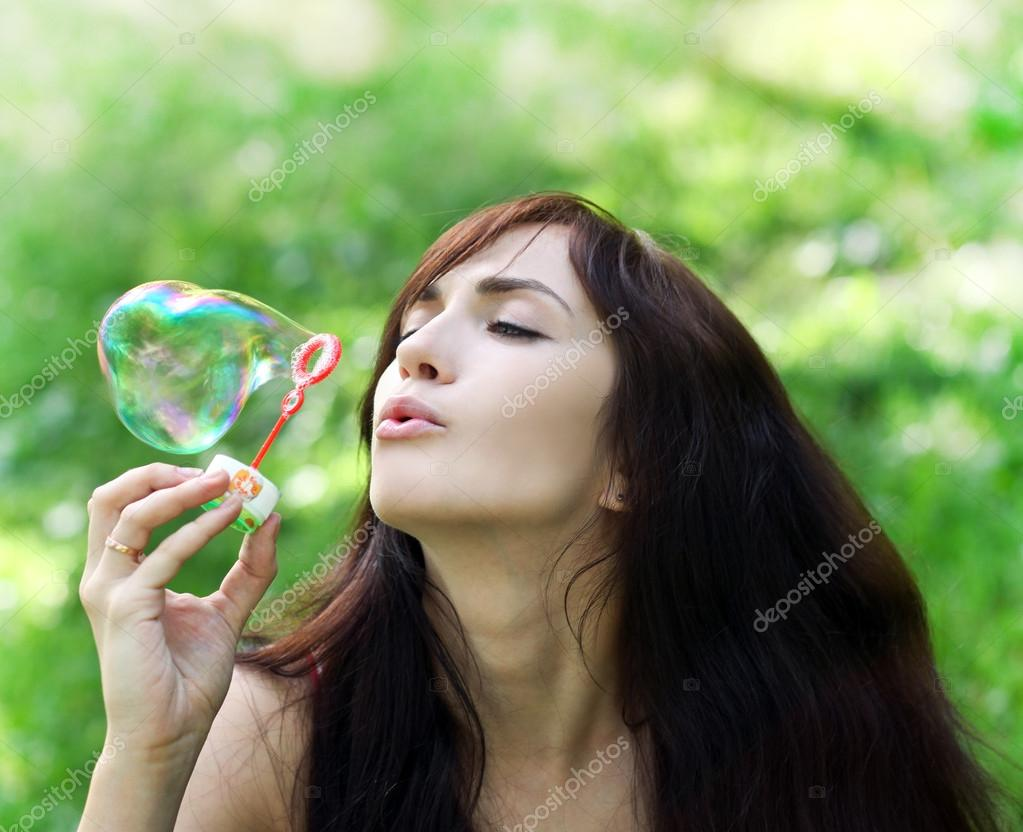 Adorable young girl inflating colorful soap bubbles in summer pa