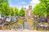 Turisté chodit kanálem v Amsterdamu