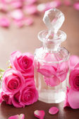 Fotografie perfume bottle and pink rose flowers. spa aromatherapy