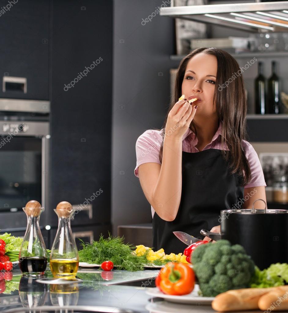 Glückliche junge frau in schürze auf moderne küche essen zu kosten beim kochen stockdatei