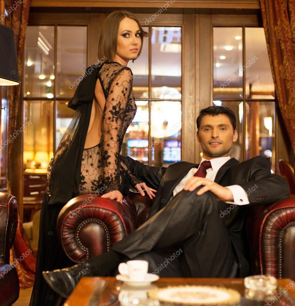 Elegant couple in formal dress in luxury cabinet interior ...