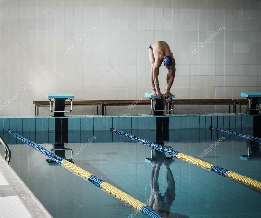 Young Muscular Swimmer In Low Position On Starting Block In A Swimming Pool Stock Photo