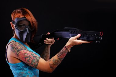 Girl with tattoos and a gun