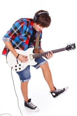 Teenage boy in headphones is playing on electro guitar