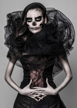 Brunette with a greasepaint of a skull in the dark atmosphere