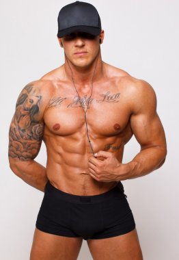 Hot guy with a well looking body is posing in pants and cap only