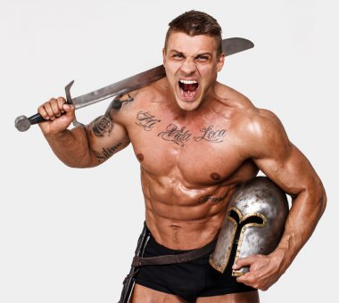 Huge shirtless warrior is screaming and holding his weapon