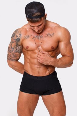 Sexy shirtless man is distracted on his mp3's wire