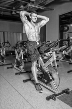 Shirtless sportsman is having workout on bicycle in gym