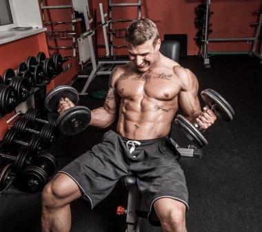 Shirtless bodybuilder is having really hard workout