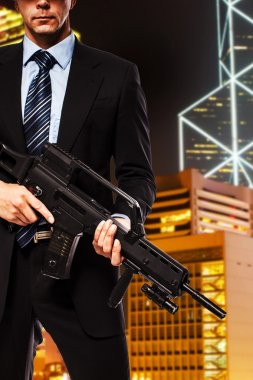 partly seen man in suit who is holding gun