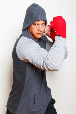 Young boxing man is posing on a white background