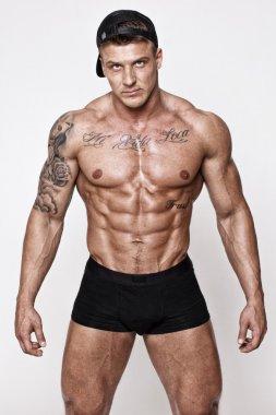 Sporty shirtless man in black cap