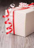 White textured gift box with red korker ribbons