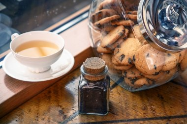 Cookies in a jar and a cup of tea on a windowsill