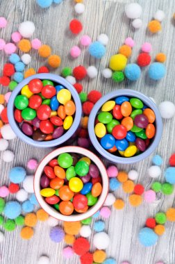 Three jars of hard color candies and felt beads around