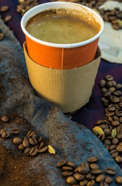 Papercup with coffee with linen and beans around