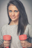 Photo Pretty girl with two dumbbells