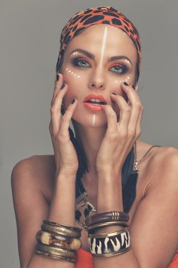 Woman with bracelets and tribal makeup
