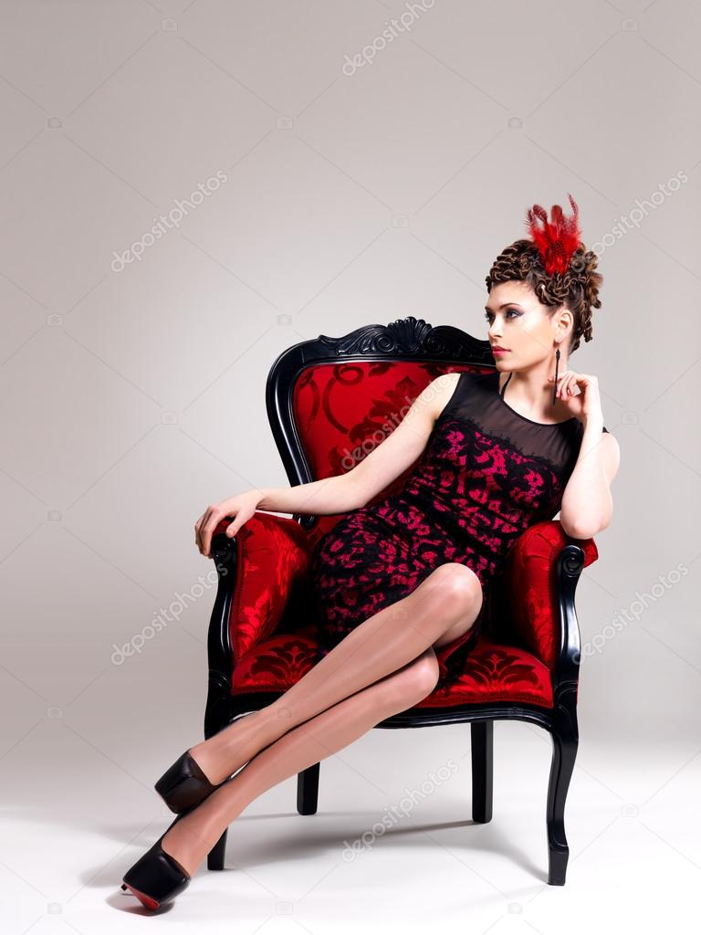 Woman With Fashion Hairstyle And Red Armchair Stock Photo