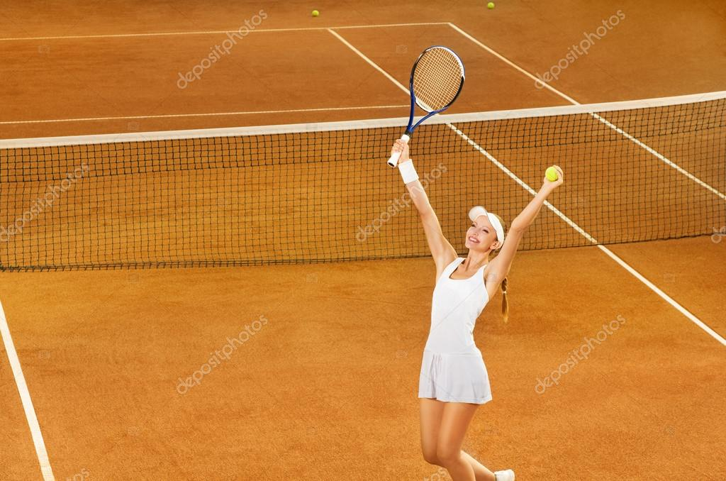 Young female tennis player celebrating victory at tennis court