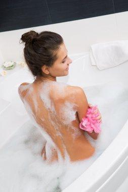 Beautiful young woman taking a bubble bath