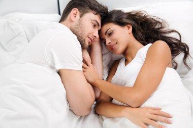 Young adult heterosexual couple lying on bed in bedroom stock vector