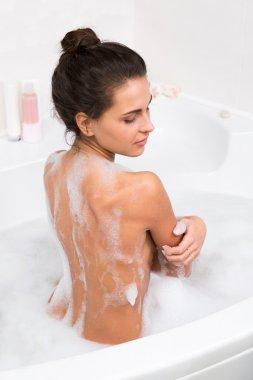 Young woman taking a bubble bath, rear view