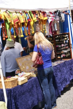 Blonde woman in blue shirt shopping at crafts stall